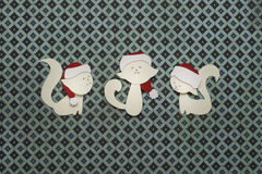 Three paper cats applique on texture background. Cute handmade cats in red hats Royalty Free Stock Images
