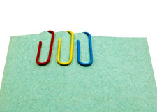 Three paper clips on the sheet of paper Royalty Free Stock Images