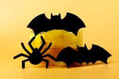 Three paper figures. Two bats and one amazing spider. All is in the black. Halloween party can start. Orange background stock photo