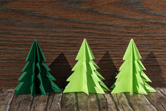 Three paper origami Christmas trees on a wooden background Stock Photos