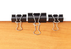 Three paperclips stapling papers. On the table Stock Image