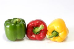 Three Paprikas. Yellow, red and green paprika on light background Royalty Free Stock Photography