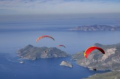 Three paragliders fly over the coastline from the top of Babadag,. Turkey Stock Images