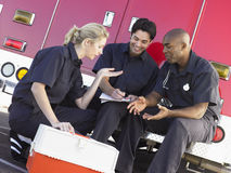 Three paramedics chatting by ambulance Stock Photo