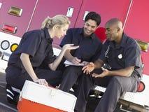 Three paramedics chatting by ambulance. Three paramedics chatting and doing paperwork, sitting by their ambulance stock photo