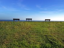 Three park benches looking out to sea. Three park benches looking out to the ocean Royalty Free Stock Photography