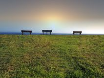 Three park benches looking out to sea. Three park benches looking out to the ocean Stock Photos