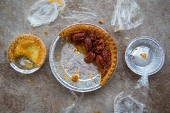 Farmer`s Market Half Eaten Pies With Plastic. Three partially eaten pies in tin pans surrounded by plastic and crumbs Stock Image