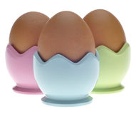 Three Pastel Egg Cups with Brown Eggs Royalty Free Stock Photo