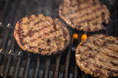 Three patties of ground meat on a cooking grate with flames and Royalty Free Stock Images