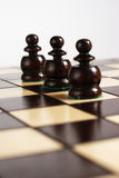 Three pawns with its reflections. On chessboard Stock Image