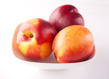Three peaches on a plate Royalty Free Stock Images