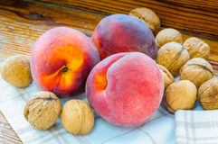 Three Peaches and Some Walnuts. Three red peaches, and some walnuts close to the window Stock Photography