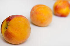 Three peaches on a white background.  Stock Image