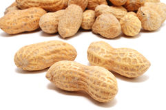 Three Peanuts. Isolated on White With Many More In the Background Stock Photo
