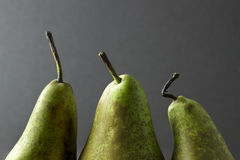 Three pear tops and stalks on a dark background Royalty Free Stock Photo