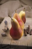 Three pear on wooden board with cinnamon and sugar. Vintage set of pears, cinnamon and sugar on brown cloth Royalty Free Stock Photos