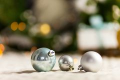 Three Pearl Christmas balls with colorful bokeh stock photography