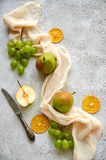 Three pears with green grapes and three dried pieces of orange decorated with silver vintage knife and light brown cloth Royalty Free Stock Image