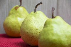 Three pears. Three green pears on a red pad Royalty Free Stock Photography