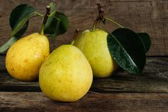 Three pears with leaves on a wooden surface Stock Photos