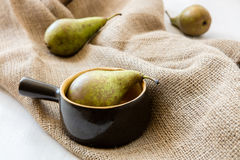 Three pears: one in clay pot two on the jute bag Stock Photo