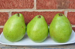 Three Pears on the white plate red brick backgroun Stock Images