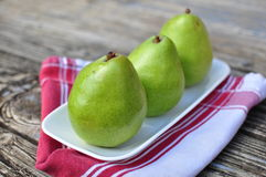 Three Pears on the white plate wooden background Royalty Free Stock Images