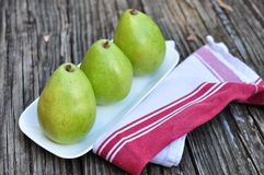Three Pears on the white plate wooden background Royalty Free Stock Photos