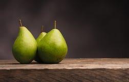 Three pears on wood Royalty Free Stock Photos