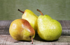Three pears on wooden table Stock Photos