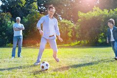 Supportive family playing soccer together. Three peas in a pod. Selective focus on a happy father and son passing a ball while playing football in a family Stock Image