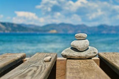 Three pebbles stacked one upon another on wooden plates Royalty Free Stock Images