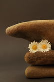 Three pebbles superimposed on each other. Decoration with stones, flowers and feather stock photo