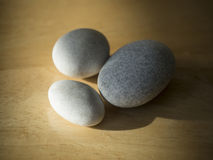 Three pebbles - white and grey on natural wood desk stock photo