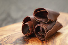 Three peeled chocolate curls on olive wood board Royalty Free Stock Images