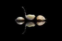 Three peeled garlic on black background Royalty Free Stock Image