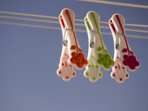 Three pegs hanging on the line. Blue background Stock Images