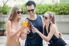 Three pelple in group of friends making party in the pool and Dr Royalty Free Stock Image