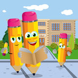 Three pencil with book pencil and schoolbag in front of a school Royalty Free Stock Image