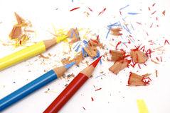 Three pencils. Bright colorful image of freshly sharpened colored pencils, red, blue and yellow, with shavings on white drawing paper Royalty Free Stock Photography
