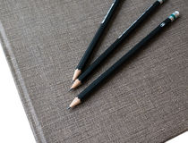 Three pencils on book Royalty Free Stock Photos