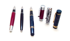 Three pens and caps. Three isolated pens over white background Stock Image