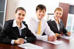 Three people. Image of three business people sitting at the table in a line stock photography