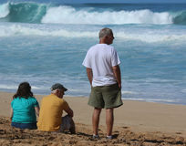 Three people on beach. Watching surfers and waves Stock Photography