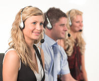 Three people in a call centre. Three working in a call centre with headsets Stock Images