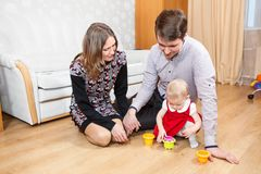 Three people Caucasian family playing on floor in room Stock Images