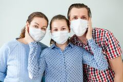 Three People Caucasian Family With Dad, Mom And Daughter Staying At Home Wearing Facial Masks, Portrait Stock Photos