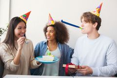 Three people are celebrating birthday. They wears funny hats. Girl is holding a plate with cake while guy has a present. In his hands and a strange thing in his stock photos