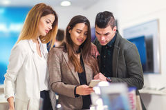 Three people are choosing smart phones Stock Photo